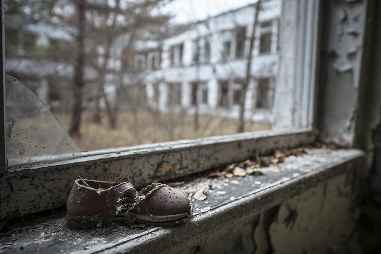 Детская обувь на подоконнике брошенного дома
